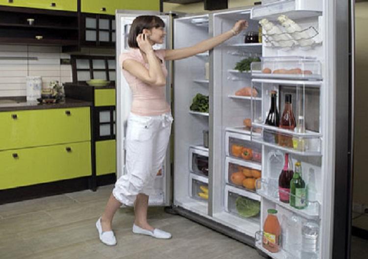 Девушка на кухне перед большим холодильником