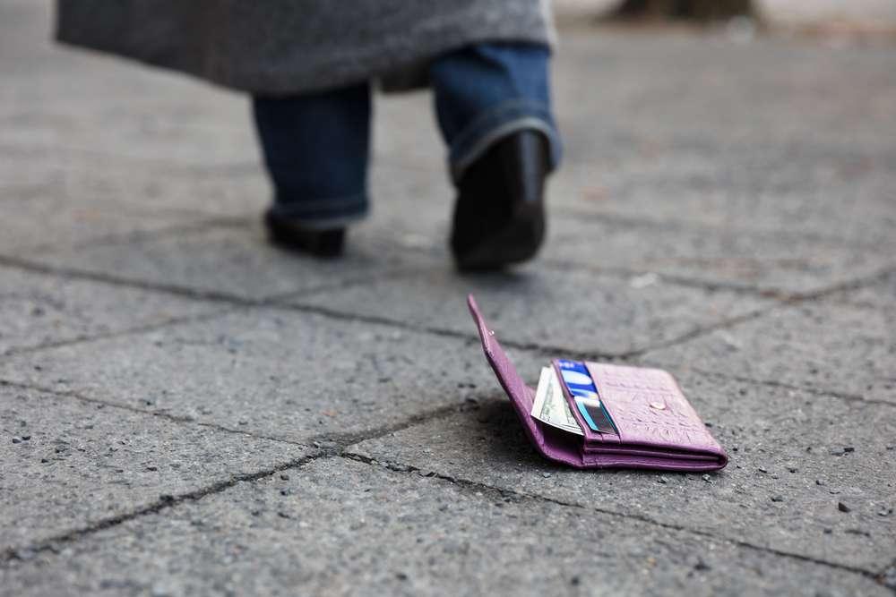 Розовый кошелек на асфальте