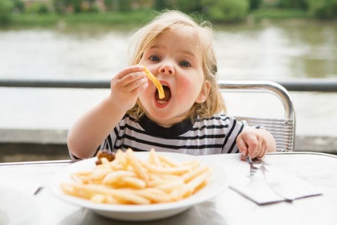 Ребенка ест картошку фри