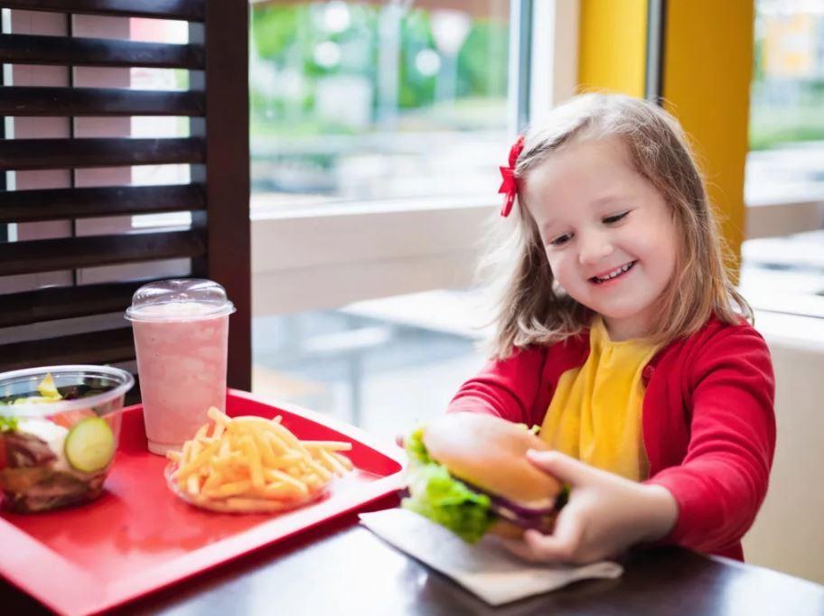 Девочка с гамбургером и картошкой фри