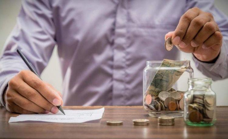 Купюры и монеты в банках и ручка в руке