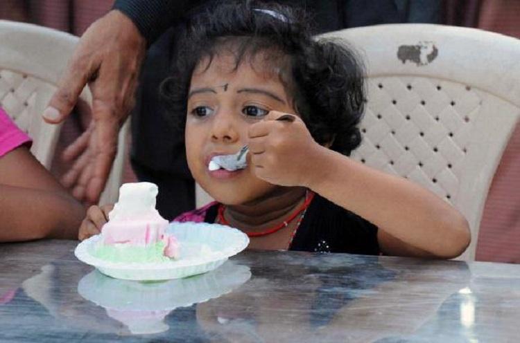Индийский ребенок ест мороженое