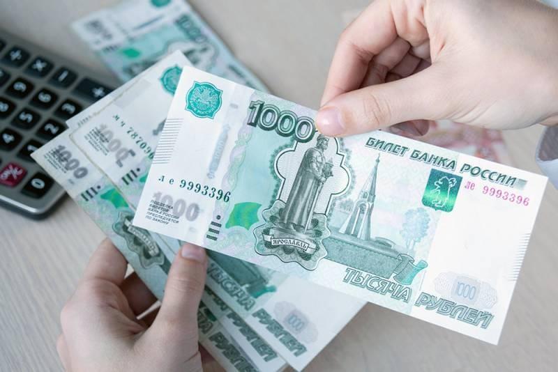 Купюры по 1000 рублей в руках и калькулятор