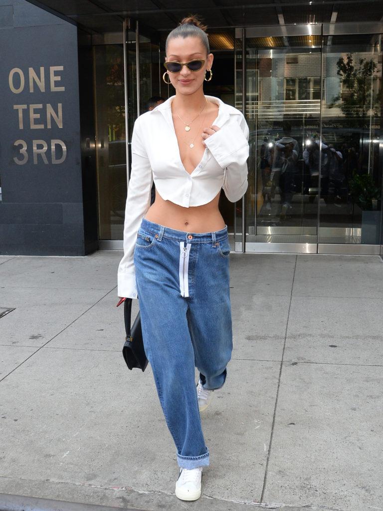 Девушка в белой блузе и джинсах с низкой посадкой
