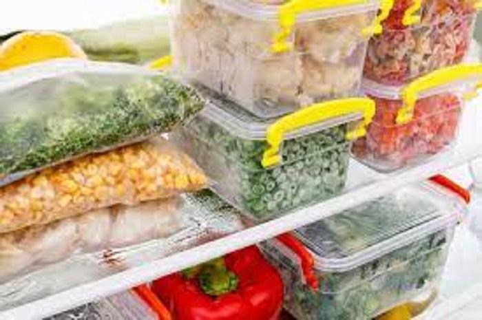Пакеты и судочки с овощами в морозильной камере