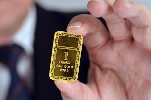 Золотой слиток 999-й пробы зажатый между пальцами