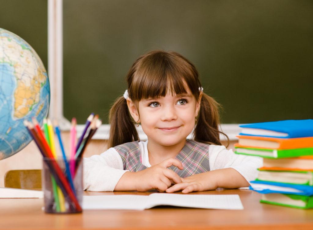 Девочка за солом, глобус и карандаши