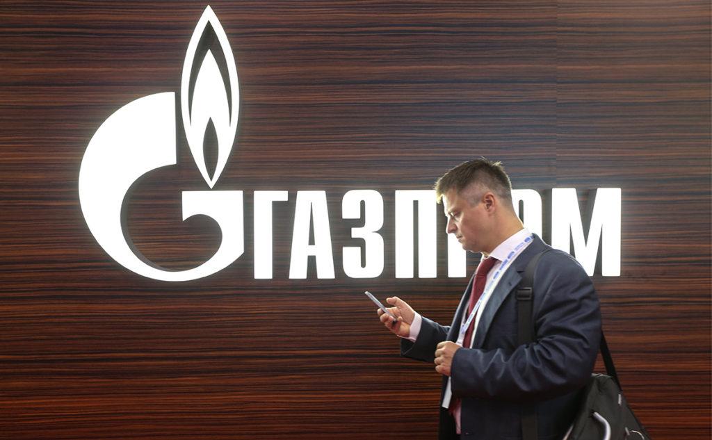Логотип Газпром и мужчина с телефоном