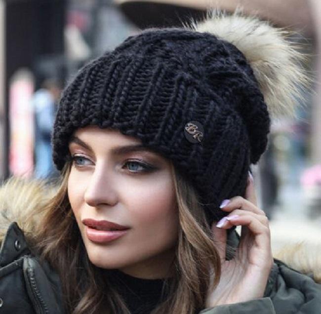 Женщина в вязаной шапке с помпоном