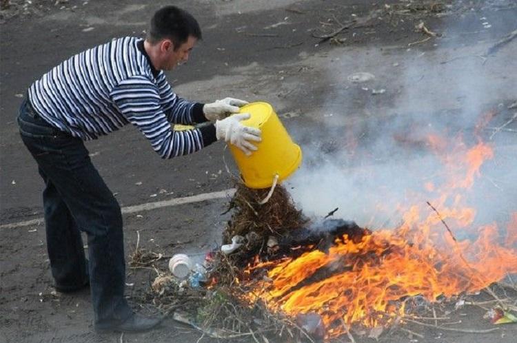 Человек высыпает мусор в костер