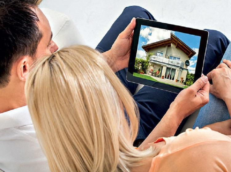 Люди смотрят на дом на планшете