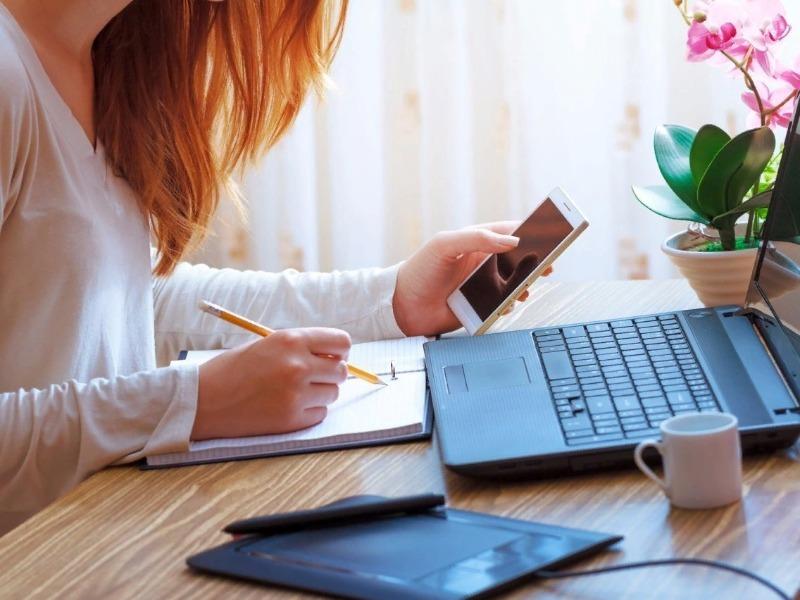 Девушка с телефоном пишет перед ноутбуком