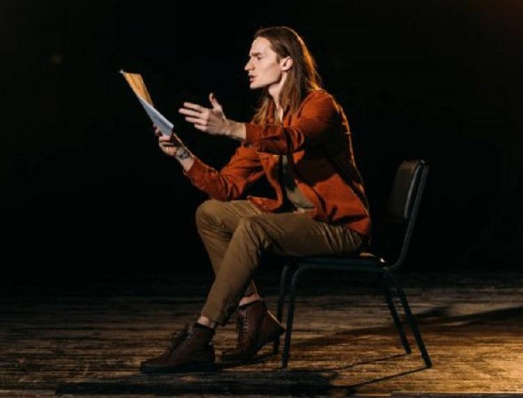 Актер на сцене на стуле