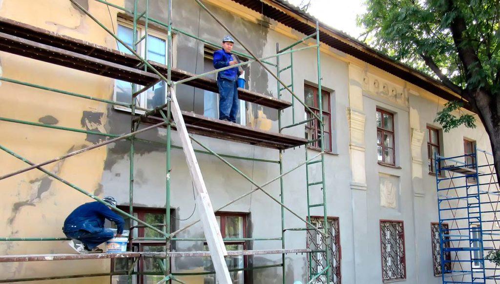Рабочие на высоте ремонтируют здание