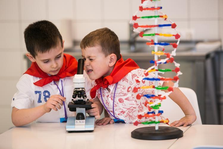 Дети в игровой смотрят в микроскоп